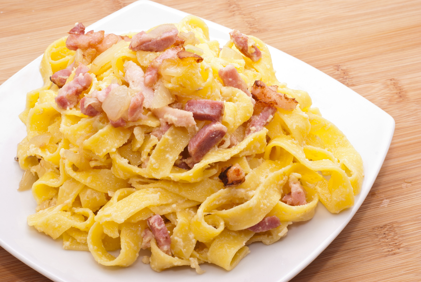 pasta Carbonara with eggs bacon and parmesan on wooden board